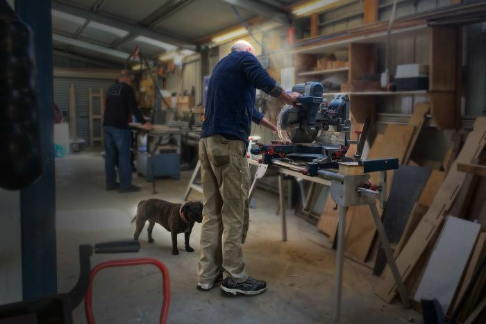 Tony Bull woodworking in a workshop.