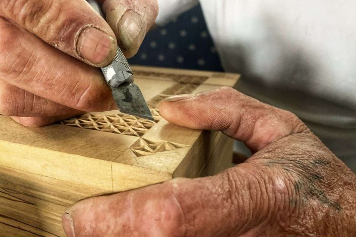 A knife carves a wooden box.