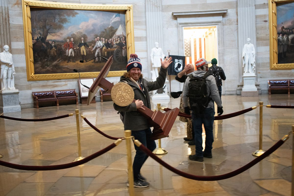 A member of the pro-Trump mob that invaded the Capitol Building carries the Speaker of House's lectern through the rotunda.